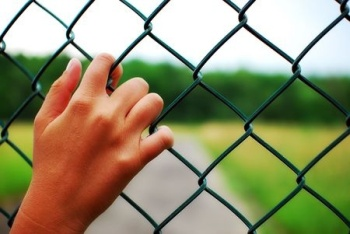 hand on chain-link fence