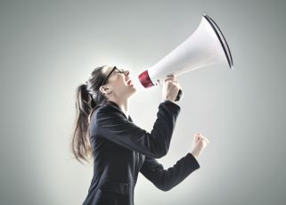 38886346 - portrait of a pretty businesswoman yelling over the megaphone